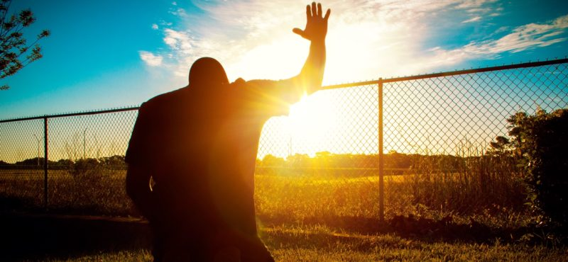 Man praying in the morning in a beautiful sunrise.